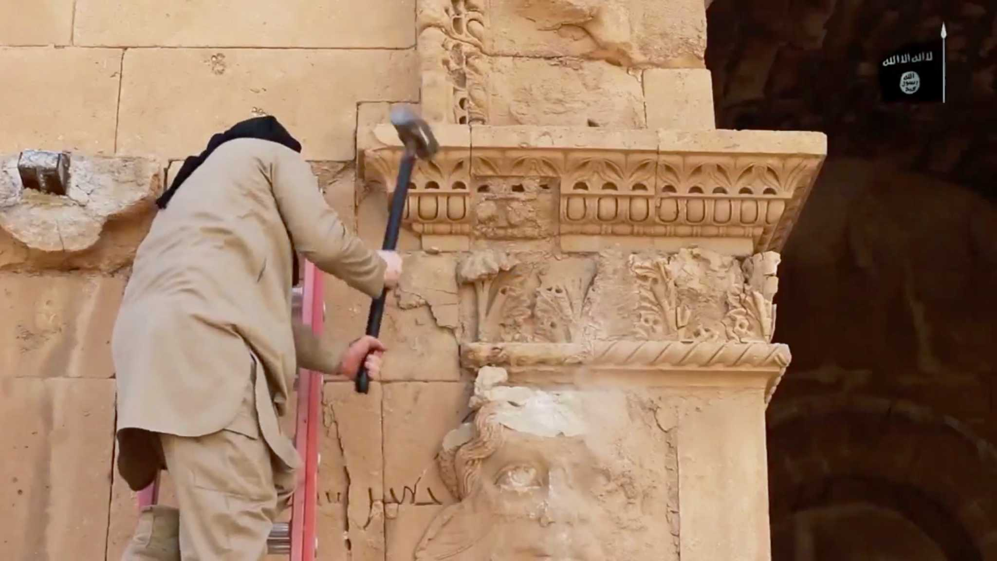 In this image made from a militant video posted on YouTube on Friday, April 3, 2015, which has been verified and is consistent with other AP reporting, a militant hammers away at a face on a wall in Hatra, a large fortified city recognized as a UNESCO World Heritage site, 110 kilometers (68 miles) southwest of Mosul, Iraq. Islamic State extremists at Iraq's ancient city of Hatra destroyed the archaeological site by smashing sledgehammers into its walls and shooting Kalashnikov assault rifles at priceless statues, a new militant video purportedly from the group shows. (AP Photo/Militant video)