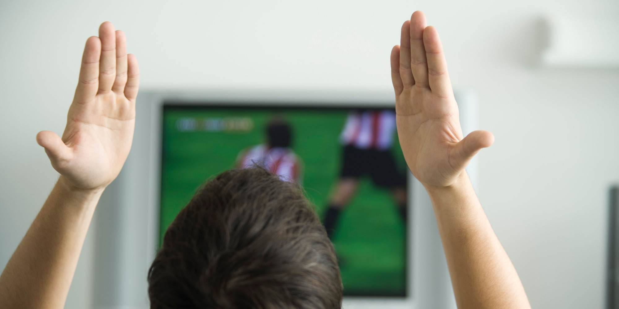 B9Y5J5 Male watching sports match on television, hands raised in air, rear view