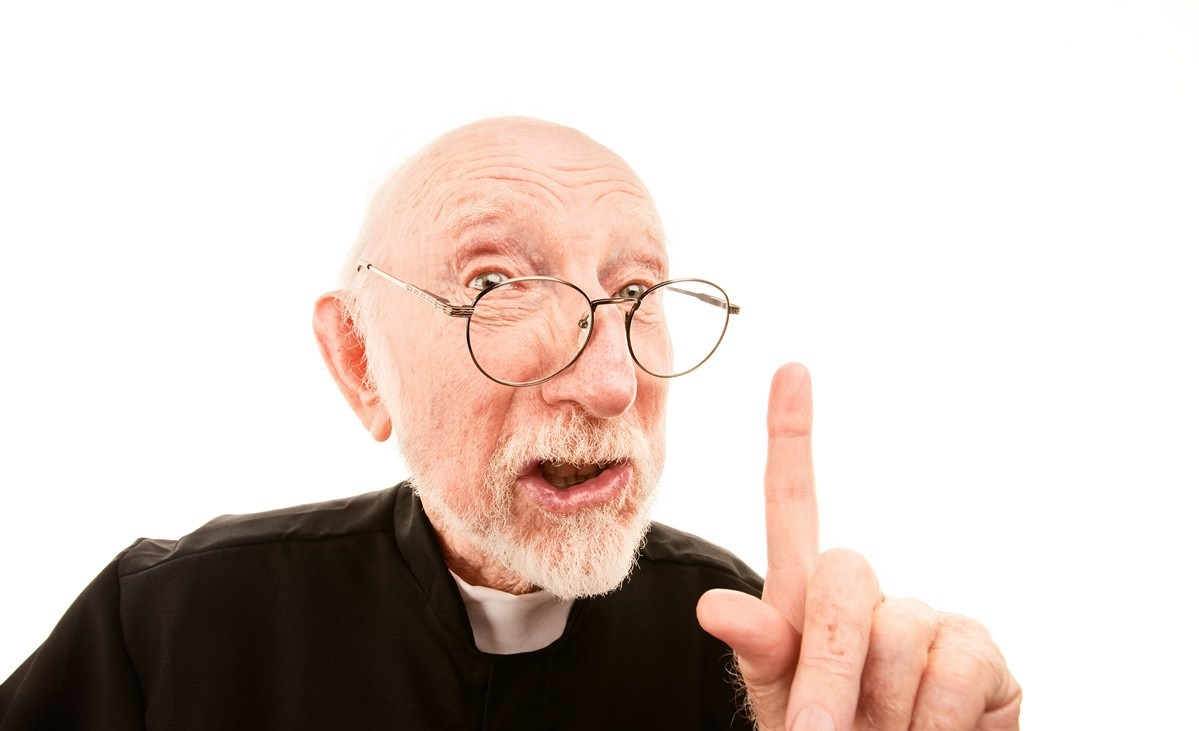Priest making admonishing gesture with finger in the air