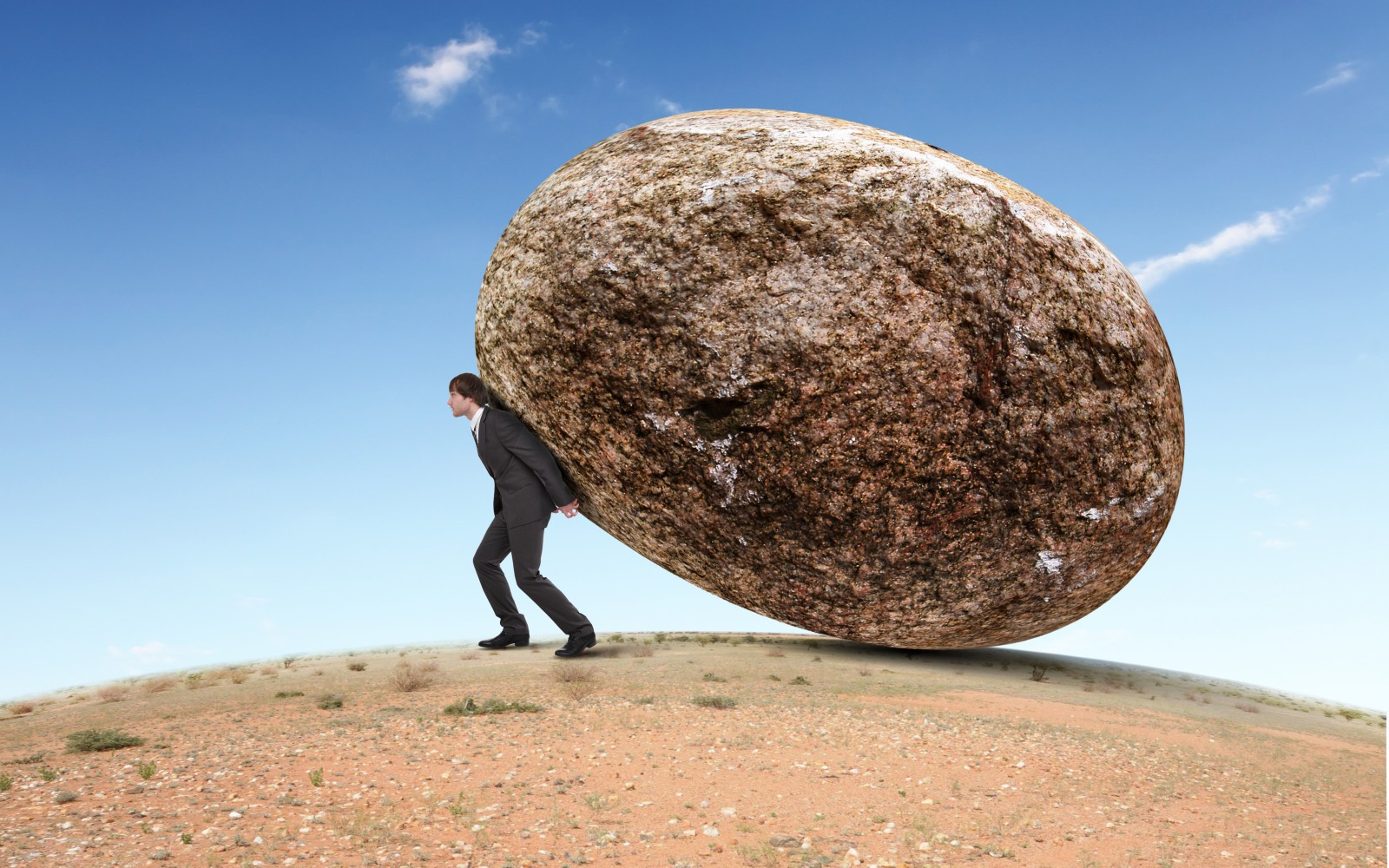 Businessman-rolling-a-giant-stone